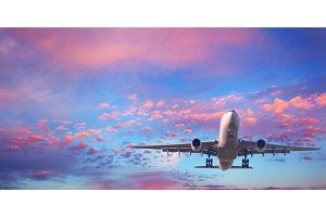 Passenger airplane is flying in the blue sky with pink clouds