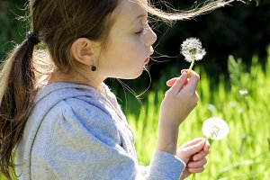 Girl blowing dandelions