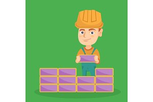 Caucasian bricklayer boy building a brick wall.