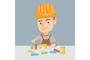 Boy playing in the builder with building cubes toy