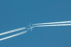 Two passengers jets at the same time in high blue sky