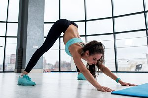 Slim fit attractive brunette girl working-out indoors performing yoga posture called downward-facing dog with panoramic window in background