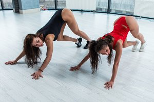 Two sexy brunette women wearing leotards doing downward dog calf stretch exercise on floor in gym during stretching class