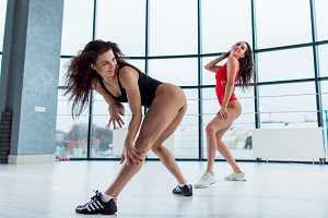 Two slim athletic female models wearing swimsuits and sneakers smiling standing in sexy playful pose or dancing indoors