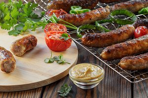 Grilled sausages and vegetables on a wooden background in rustic style. Top view