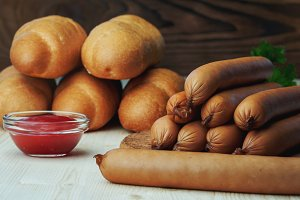 Ingredients for making homemade hot dogs. Sausages, fresh baked buns and ketchup sauce