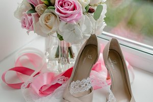 Wedding bouquet with pink ribbons and shoes