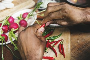 hands with chilli pepper on wooden