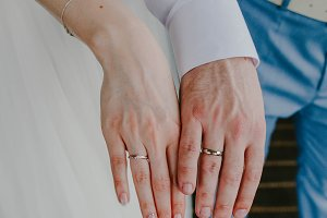 Wedding rings at the hands of the bride and groom