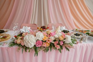 Pink flowers on the table by newlyweds