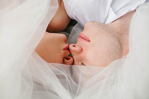 The bride and groom to be covered by the veil. Kiss
