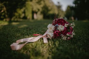 Bridal bouquet in red shades on the grass