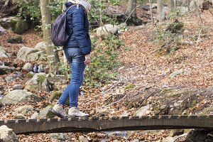 Woman walks on wooden bridge