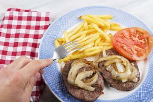A hand with fork on french fries and hamburger with onion and tomato on blue plate next to napkin on wooden table. Food.