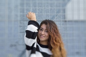 young woman leaning on metal net