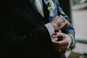 The groom wears cufflinks