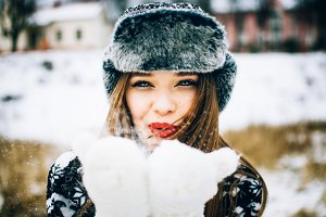 Young woman blows snow