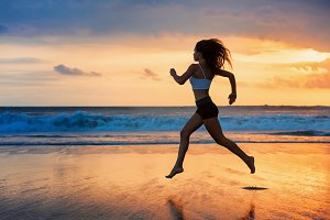 Girl running by sunset beach