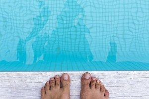 male feet at swimming pool