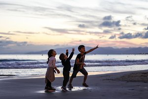 Silhouette of three kids playing