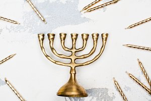 Traditional golden Hanukkah candleholder and candles on white ba