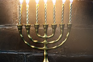 Traditional golden Hanukkah candleholder and candles on dark bac