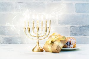 Happy Hanukkah background with menorah, burning candles and donu