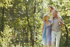 Father - bold man, mother - blonde beautiful woman and little girl - walking in the park at sunny day