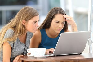 Two worried girls watching online