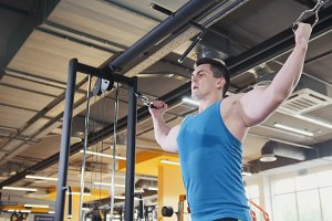Bodybuilder training in the gym - young muscular man perform training for biceps, slider shot