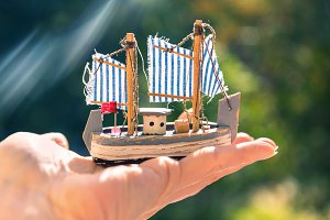 Toy wooden tall ship in the hand