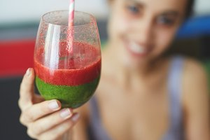 smiling woman with glass of strawberry smoothies with a green cocktail