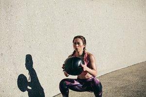 Sportswoman doing squat exercises