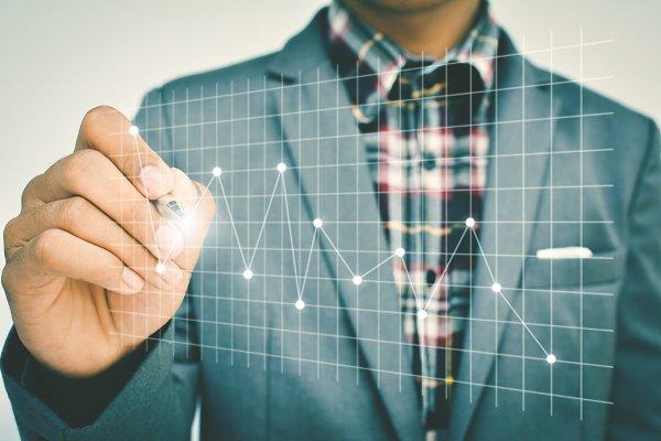 businessman drawing financial graph
