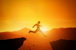 Man jumping from one rock to another. Sunset mountains scenery