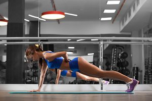 Attractive young woman is doing push ups exercise while working out in gym