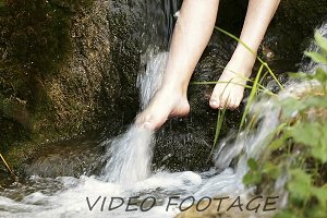 Teenager with feet in the water