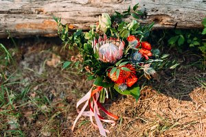 A rustic wedding bouquet with pink ribbons near the log