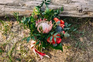 A rustic wedding bouquet with pink ribbons near the log. Artwork