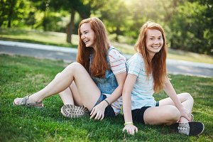 Pair of identical twins ginger sisters having fun outdoor in the park. Coincidence or hard work of parents. Friendship concept.