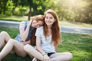 Ginger twin girls having a great day outside in the park on a sunny summer day. Youth friendship and careless time spent together.