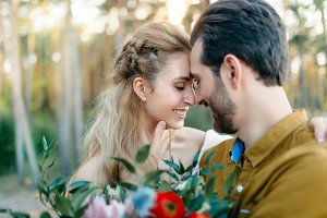 A young couple smile and touching foreheads. Autumn wedding ceremony outdoors. Bride and groom look at each other with tenderness and love. Close-up portrait