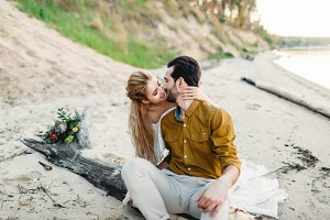 A young couple kisses on the beach. Bride and groom hugging on the log. Close-up portrait