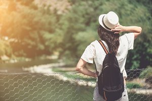 Rear view of brunette girl in park in straw hat.