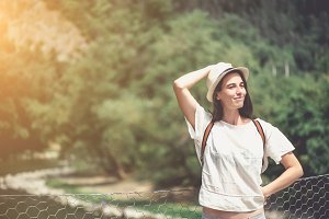 Brunette girl in park in straw hat.