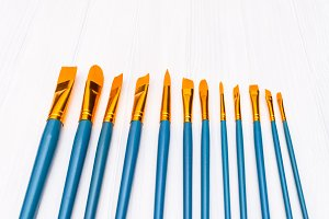 Brushes on white wooden background