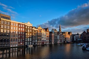 Hhouses and tourist boats on Amsterdam canal pier Damrak on suns