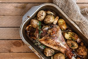 Oven baked turkey leg with potato and spices, rustic style, top view