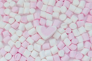 Pink and white mini marshmallows background with heart