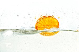 orange halves falling into water on white background.